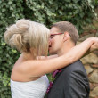 Groom kissing bride on their wedding day. — Stock Photo