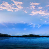 Abstracte zonsondergang achtergrond met bos meer en wolken — Stockvector