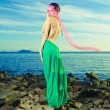 Lady in green dress on seashore - Stock Photo