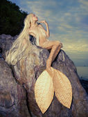Beautiful mermaid sitting on rock — Stok fotoğraf