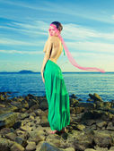 Lady in green dress on seashore — Stockfoto