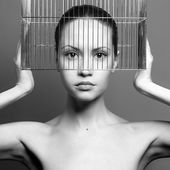 Surrealistic portrait of young lady with cage — Stock Photo