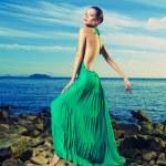 Lady in green dress on seashore — Stock Photo