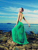 Lady in green dress on seashore — Stock Photo