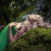 Beautiful lady in the coniferous forest — Stock Photo