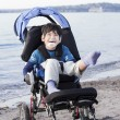Happy disabled boy in wheelchair on the beach — Stock Photo #11616702