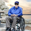 Elderly senior man in wheelchair sitting outside — Stock Photo