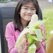 Girl peeling husk off corn cob - Stock Photo