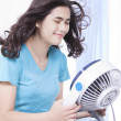Beautiful young woman or teen enjoying cool fan breeze — Stock Photo
