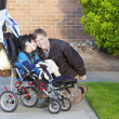 Disabled boy in wheelchair and his caretaker - Stock Photo
