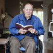 Elderly man in wheelchair at his front door reading the Bible - Stock Photo