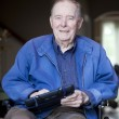 Elderly man in wheelchair at his front door - Stock Photo