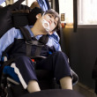 Disabled little boy sitting in wheelchair on school bus - Foto Stock
