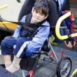 Disabled little boy on school bus wheelchair lift - Stock Photo