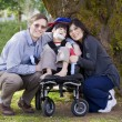Disabled child surrounded by parents - Stock Photo