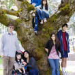 Family of seven by large cherry tree in full bloom - Stock Photo