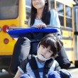 Big sister pushing disabled brother in wheelchair at school - Stock Photo