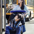 Big sister pushing disabled brother in wheelchair at school — Stok fotoğraf