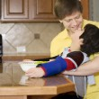 Father helping disabled son with work in the kitchen — Stockfoto