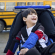 Disabled five year old boy in wheelchair, by schoolbus — Stockfoto