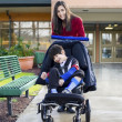Teenage girl pushing little disabled boy in wheelchair — Stock Photo #13349117