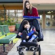 Teenage girl pushing little disabled boy in wheelchair - Stock Photo