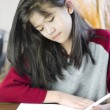 Ten year old girl writing or drawing on paper - Stock Photo