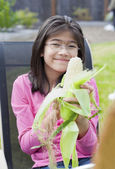 Girl peeling husk off corn cob — Stock Photo