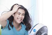Beautiful young woman or teen enjoying cool fan breeze — Stock Photo