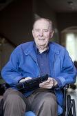 Elderly man in wheelchair at his front door — Stock Photo