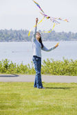 Biracial asian girl flying kite by the lake — Stock Photo