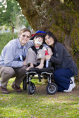 Disabled child surrounded by parents — Stock Photo
