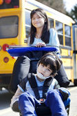Big sister pushing disabled brother in wheelchair at school — Stock Photo