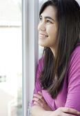 Side profile of teen girl or young woman looking out window — Stock Photo