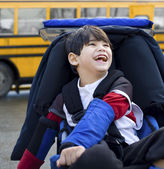 Disabled five year old boy in wheelchair, by schoolbus — Stock Photo