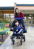 Teenage girl pushing little disabled boy in wheelchair — Stock Photo