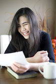 Teenage girl or young woman happily reading note in hand — Stock Photo