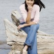 Foto Stock: Beautiful biracial teen girl sitting on fallen log by lake shore in summer