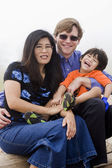 Mutiracial family sitting on beach — Stock Photo