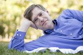 Pohledný podnikatel odpočívat na trávě — Stock fotografie