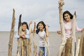 Three sisters playing by the lake shore in summer, by logs — Stock Photo