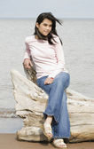 Beautiful biracial teen girl sitting on fallen log by lake shore — Stock Photo