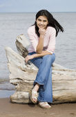 Beautiful biracial teen girl sitting on fallen log by lake shore in summer — Stock Photo
