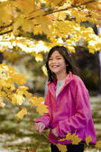 Little biracial asian girl standing amongst bright autumn leaves — Stock Photo