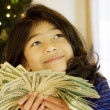 Little girl holding up large amount of cash at Christmas - Stock Photo