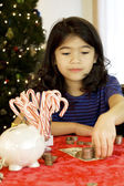 Little girl counting money at Christmas — Stock Photo