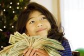 Little girl holding up large amount of cash at Christmas — Stock Photo