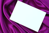 Blank white card on purple satin — Стоковое фото