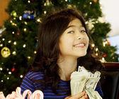 Little girl holding up cash — Stock Photo