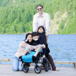 Disabled boy in wheelchair surrounded by family on lake pier - Foto Stock